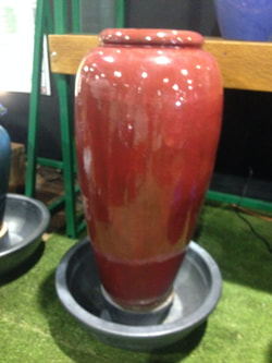 Picture of a lavish, slim red jar fountain.