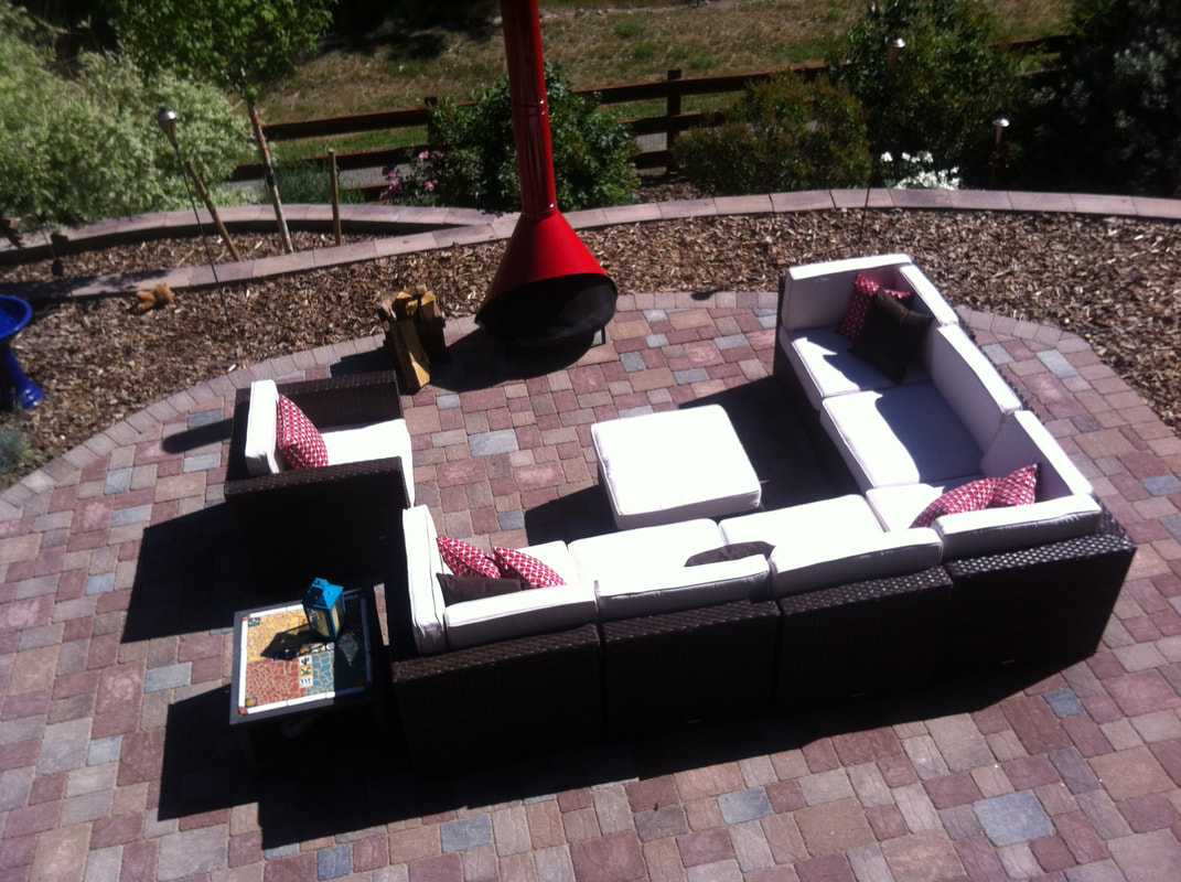 Photo of a brick patio with outdoor furniture and red fire feature.