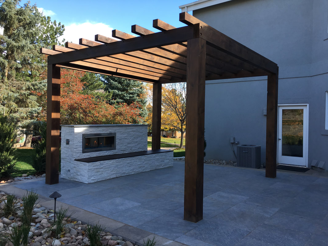 Picture of a modern Denver landscape design with a pergola and outdoor fire place.